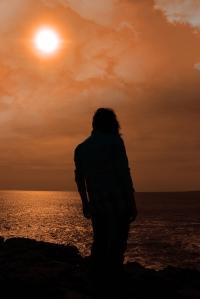 silhouette of a sad lone woman on irish cliff edge